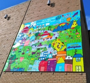 Designed by all 568 students at Parson Hills Elementary School in Springdale – and documented by Springdale's Helen Tyson Middle School EAST Initiative students – this mural is mounted on the east wall of First Security Bankin Shiloh Square. It faces the Razorback Greenway Trail, as well as what will become a public gathering green space. (photo by Jamie Smith)