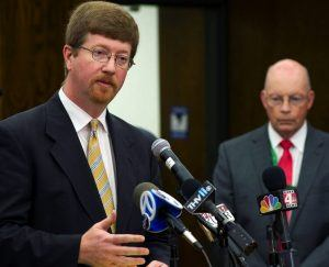 Arkansas Education Commissioner Johnny Key speaks with reporters after announcing that Little Rock Public Schools Superintendent Baker Kurrus (background) is being removed from the post. (photo from content partner KUAR)