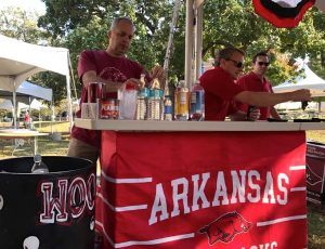 (from left) Tusk to Tail stalwarts Dale Cullins and David Rice prep the tailgate bar prior to the game in Fayetteville against Ole Miss.